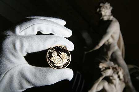 A római istent Neptunuszt ábrázoló 100 font névértékű emlékérme a királyi pénzverde olimpiai sorozatából. Az 1 kilós érme dizájnja még nem készült el.