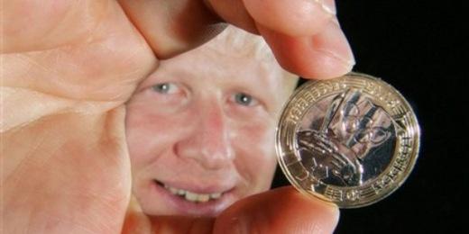Boris Johnson, London polgármestere kezében az olimpiai átadási ünnepség emlékére 2008-ban kiadott 2 font névértékű emlékérmével