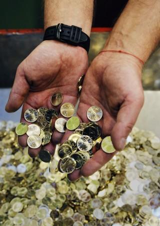Ötforintos érmék a verőgép gyűjtőtálcáján a Pénzverő Zrt.-ben. (MTI)
